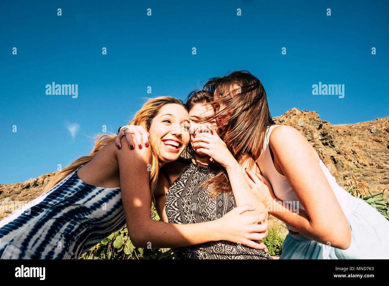 group of 25 years old girls hug and laugh together in a friendswhip teamwork. Sunny day of vacation or free time for a group. Beauty females. - Stock Image