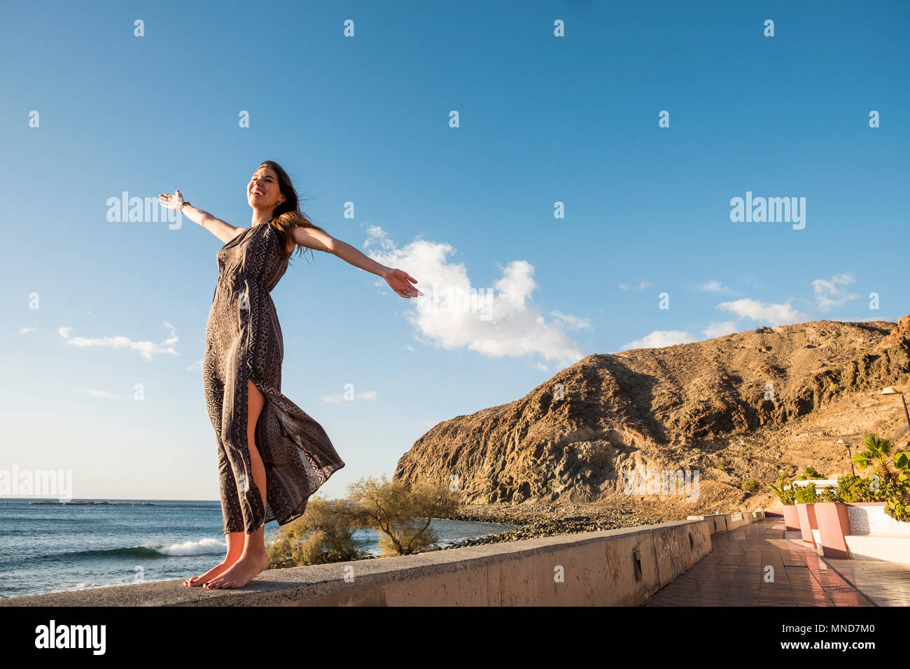 Young nice woman enjoy her freedom opening arms. Independent life and great feel with the world. Embrace all with satisfaction. Tenerife soul. - Stock Image