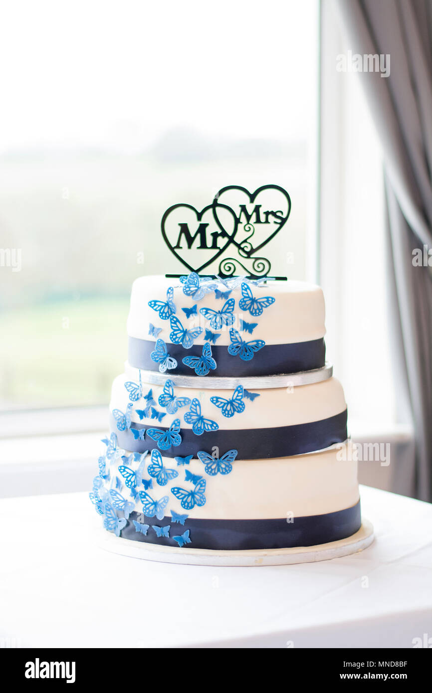 Mr Mrs White And Blue Wedding Cake With Blue Ribbon Next To A Window