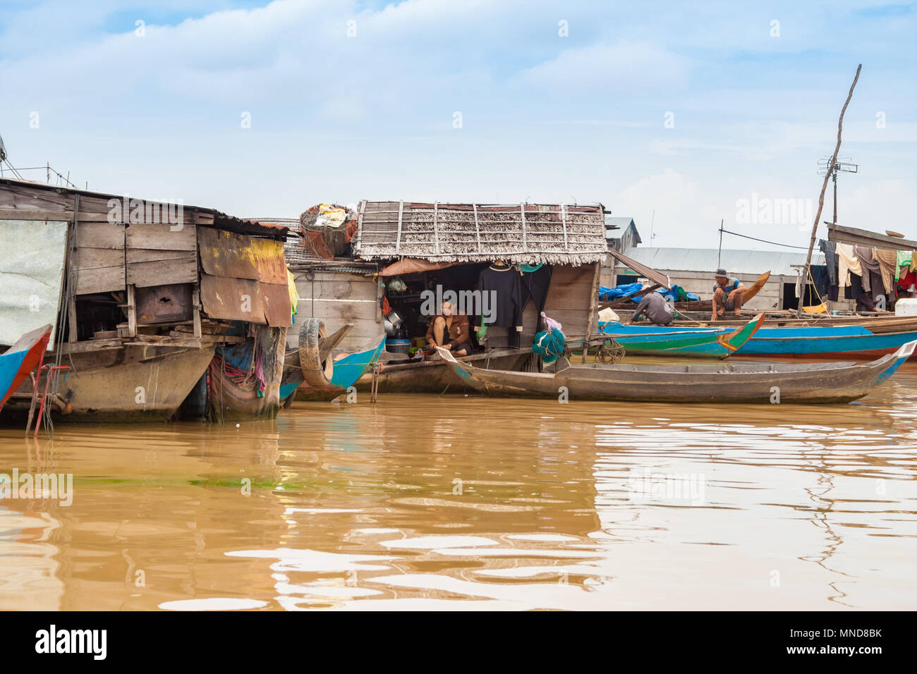 A local woman preparing something in the kitchen of a wooden houseboat with a thatched roof. Taken in May 2009 in the floating village Chong Kneas. - Stock Image