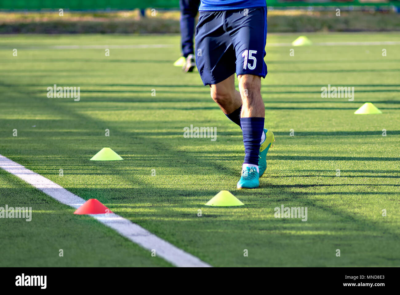 Soccer football players during the team training before the match. Exercises for football soccer youth team. Player exercises with ball and marker cones - Stock Image