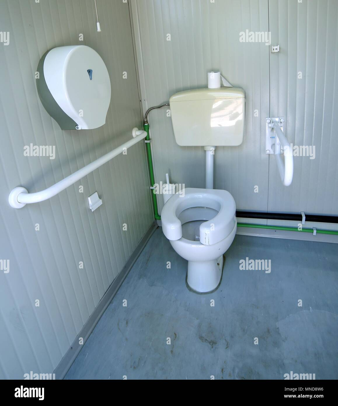 disabled bathroom with the special water closet and support bar ...