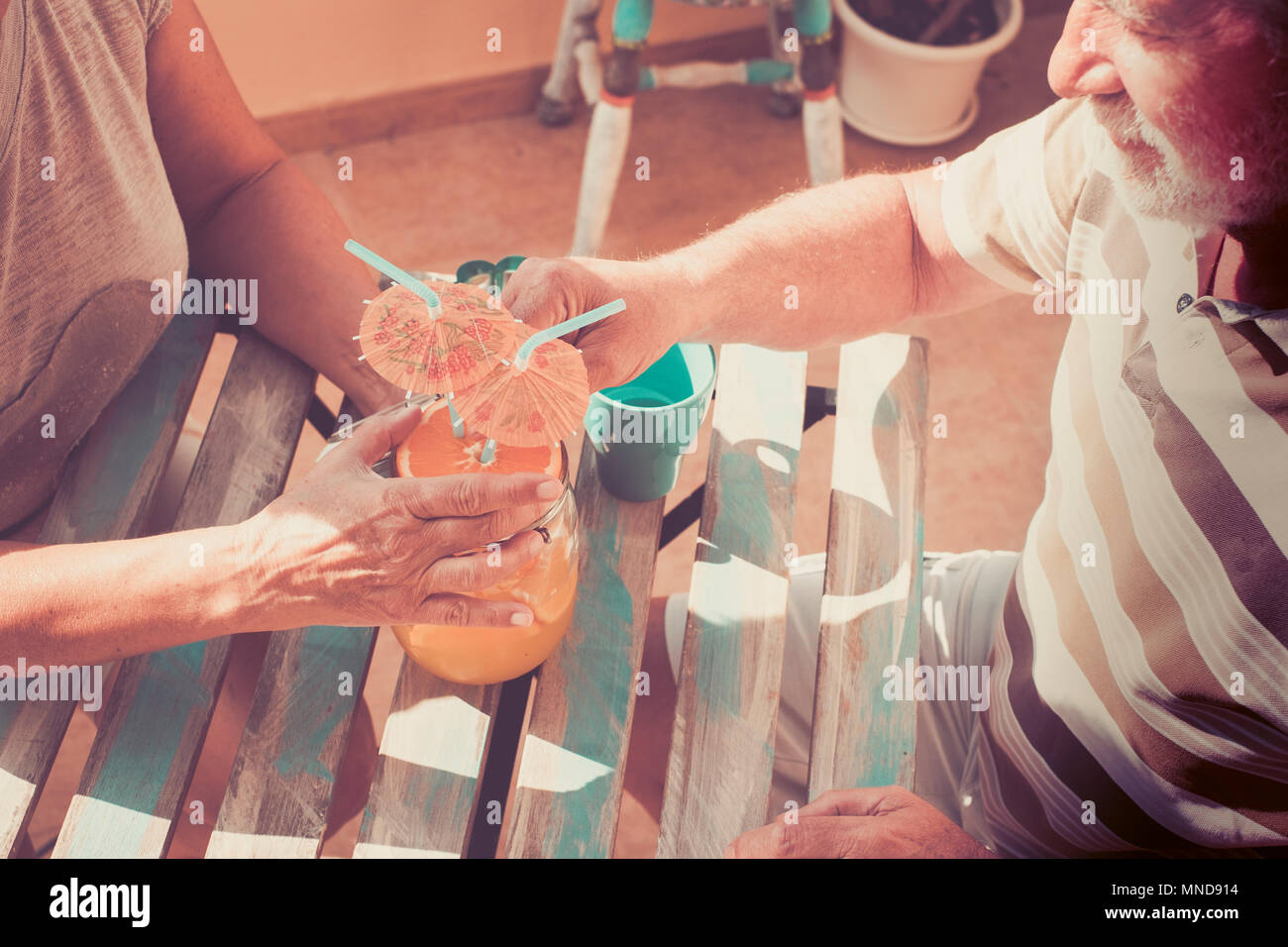 Summer time for a couple of senior man and woman drink a fruit cocktail together in vacation. Old vintage style. - Stock Image
