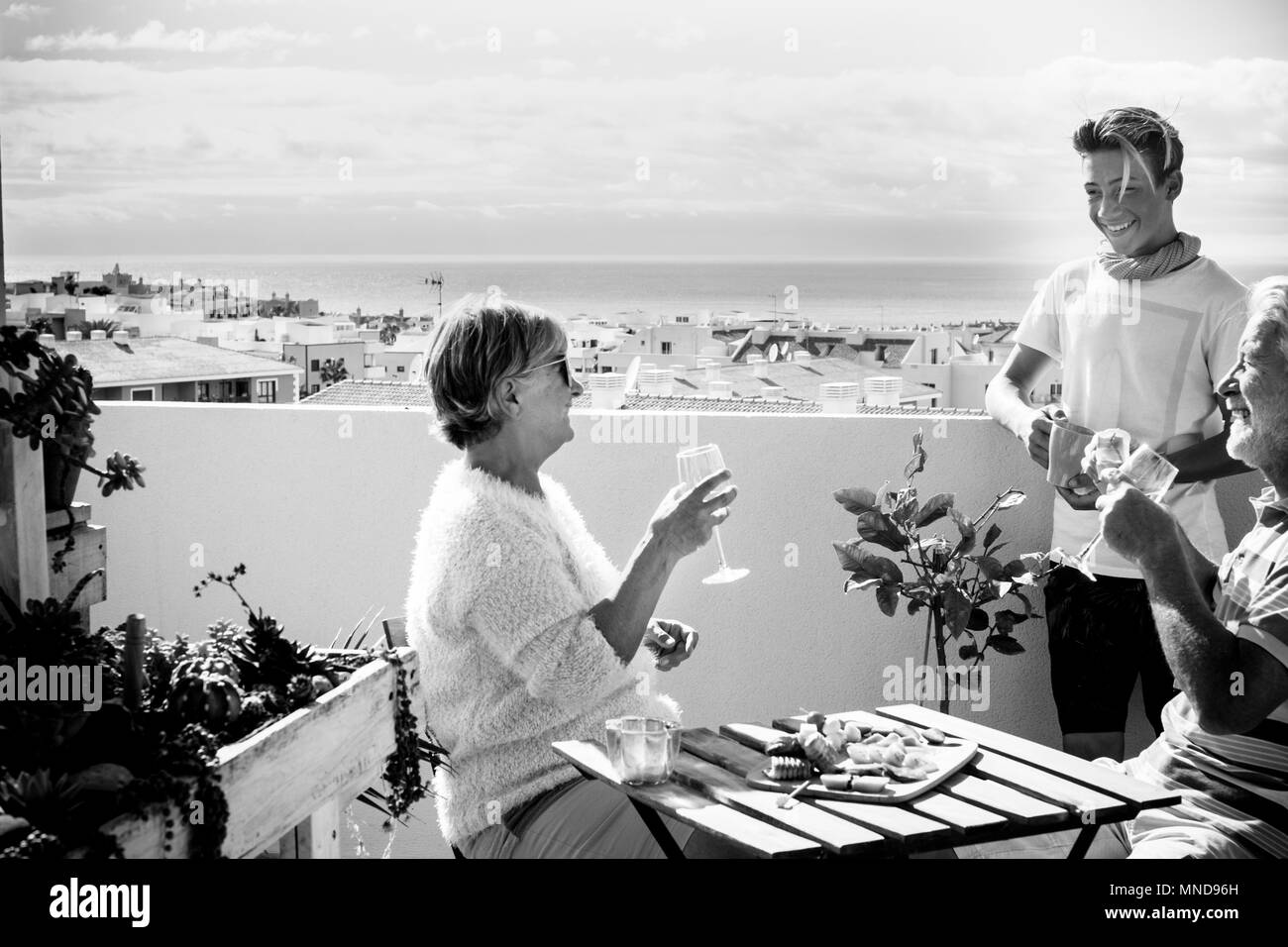 grandfathers and nephew blonde young stay on the terrace drinking and eating food on the table. amazing ocean view and clear sky for black and white i - Stock Image