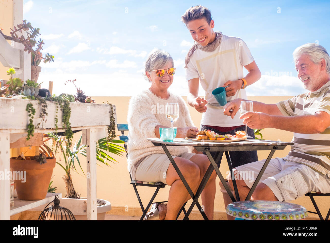 grandfather and grandmother and boy nephew having nice time leisure activity outdoor at the terrace rooftop. sunlight for summer concept or nice retir - Stock Image
