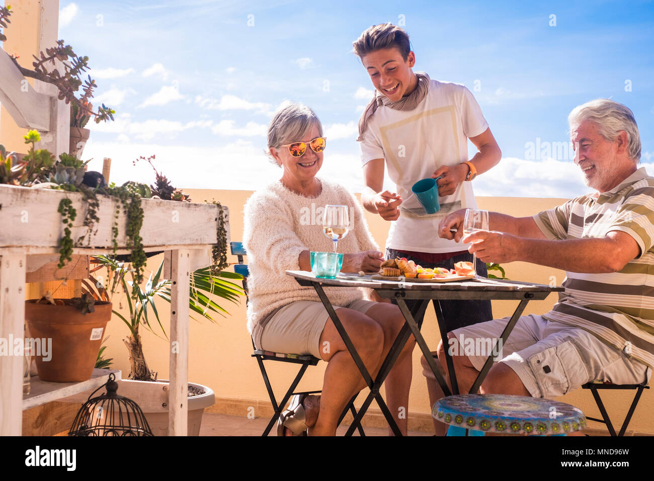 A 70-year-old senior and a 14-year-old boy can enjoy the sunny day outdoors on a terrace with food and drink. The blue sky is the background. - Stock Image