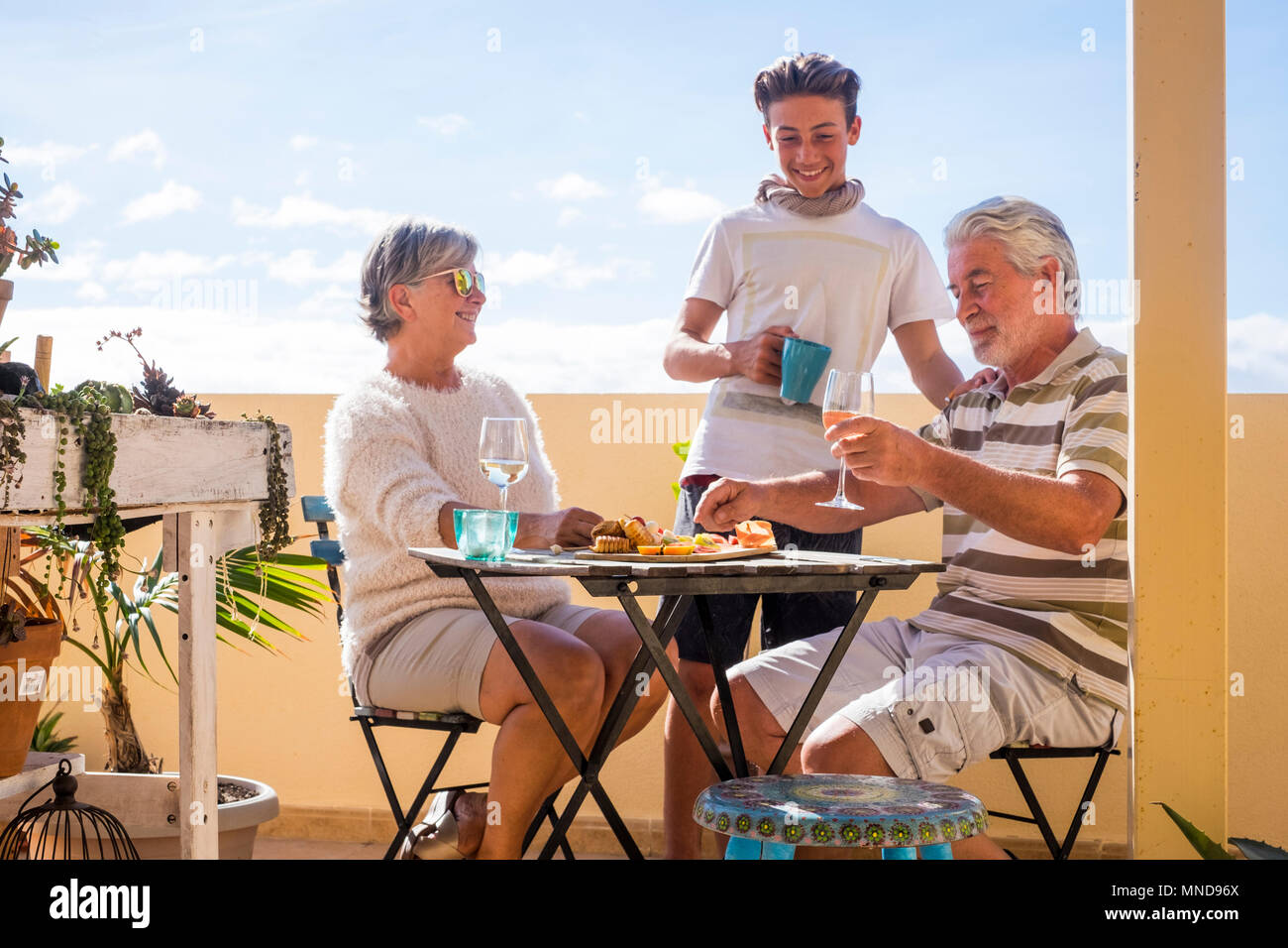 family of different ages with grandparents and grandson spend free time on the terrace eating and drinking on an outdoor terrace in summer - Stock Image