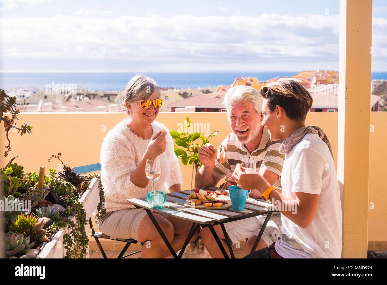 three people different ages eating and enjoying together the rooftop with sea view. Summer lifestyle with amazing panorama. Eat and drink food and bev - Stock Image