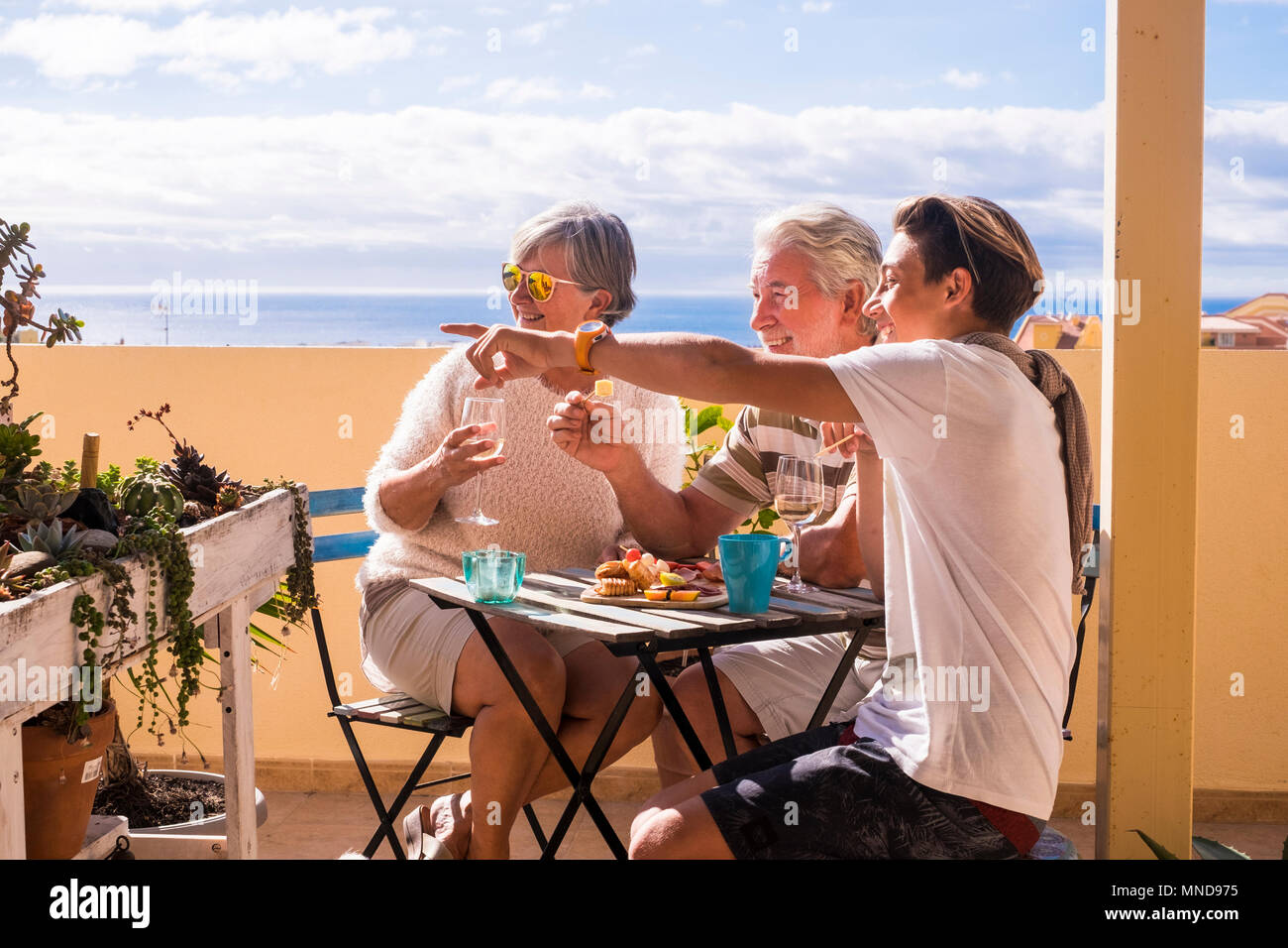 couple of grandfathers with young boy teen stay together in the rooftop with ocean view in vacation. Nice time for breakfast or brunch in a sunny day - Stock Image