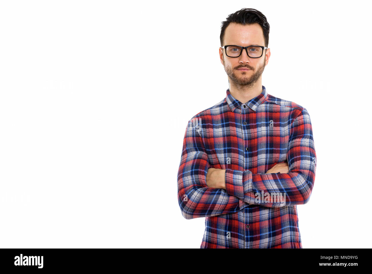 09b15a79d27 Studio shot of young man wearing eyeglasses with arms crossed Stock ...