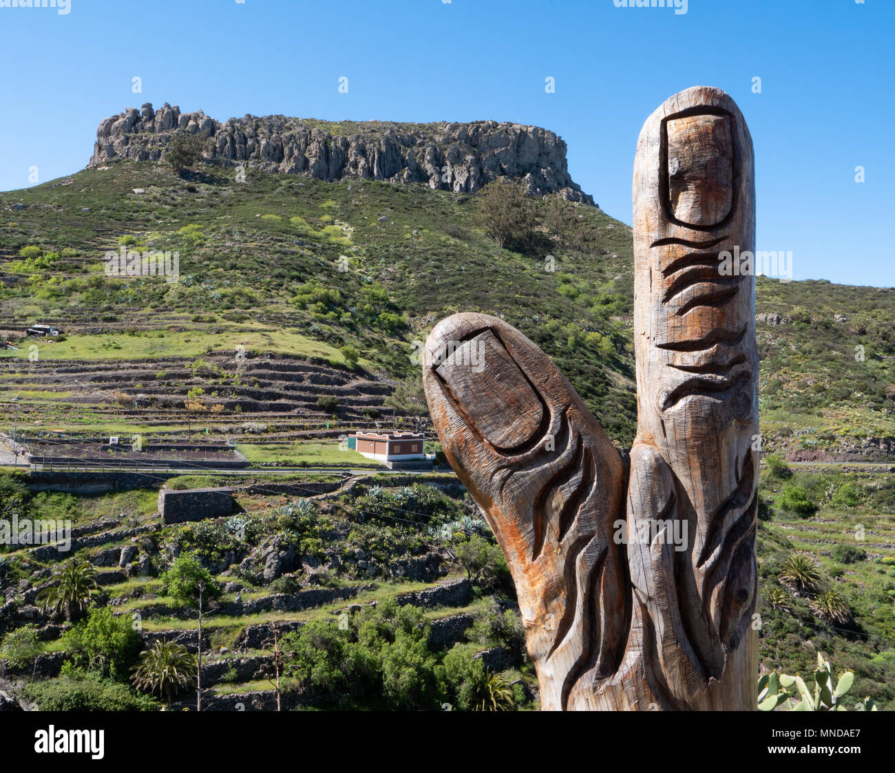 Wooden finger sculpture with the Fortaleza de Chipude a volcanic plug and natural fortress overlooking the western coast of La Gomera Canary Islands - Stock Image