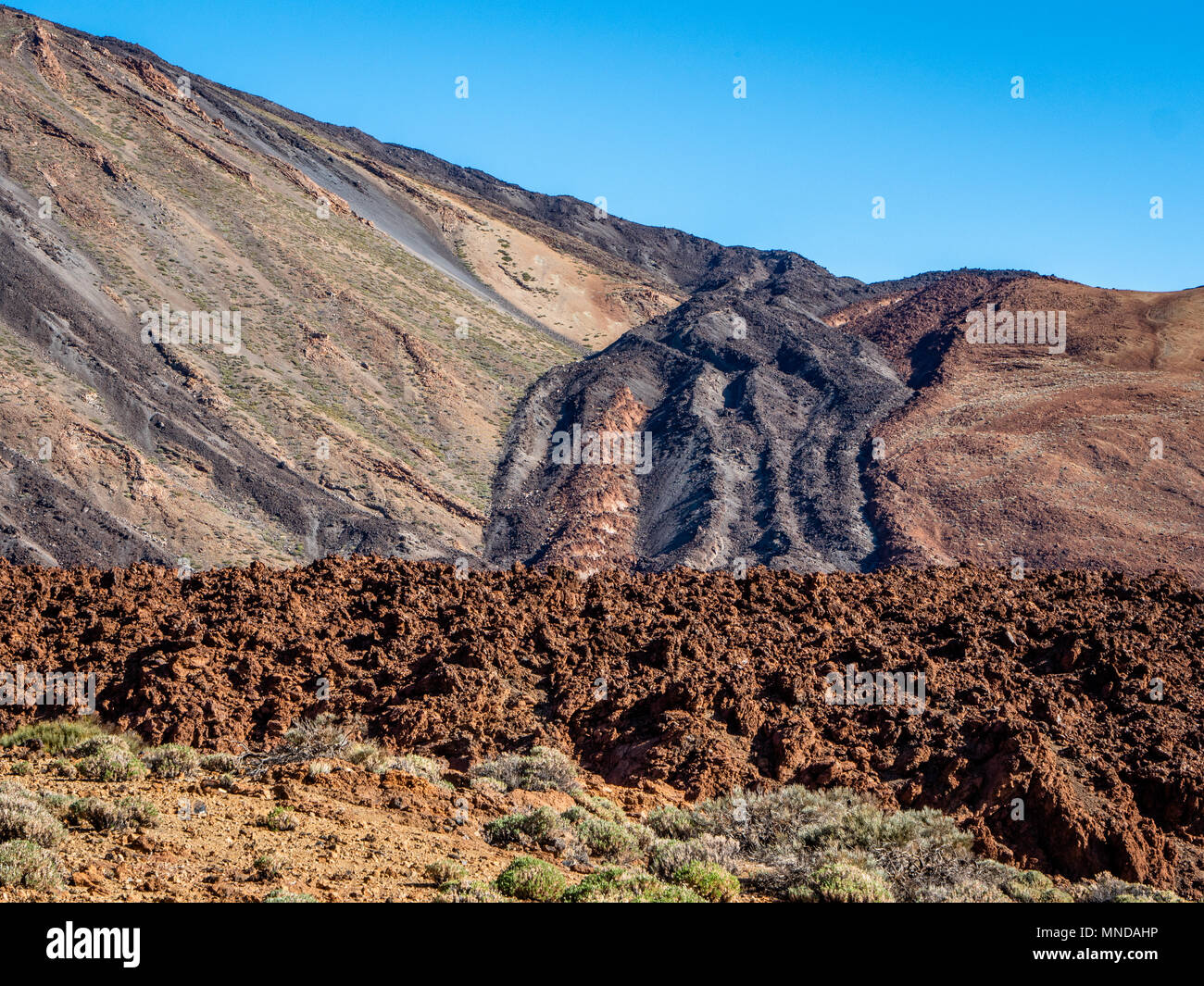 Old lava flow solidified in its descent of the cone of Teide volcano with weatherd aa lava front in foreground - Tenerife Canary Islands - Stock Image