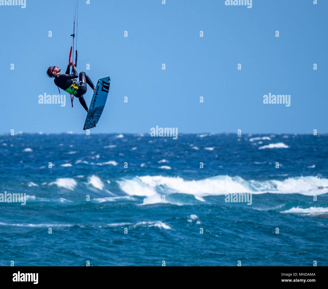 Kitesurfer in vertical ascent at the popular surfing beach of Playa del Medano on the coast of southern Tenerife Canary Islands - Stock Image