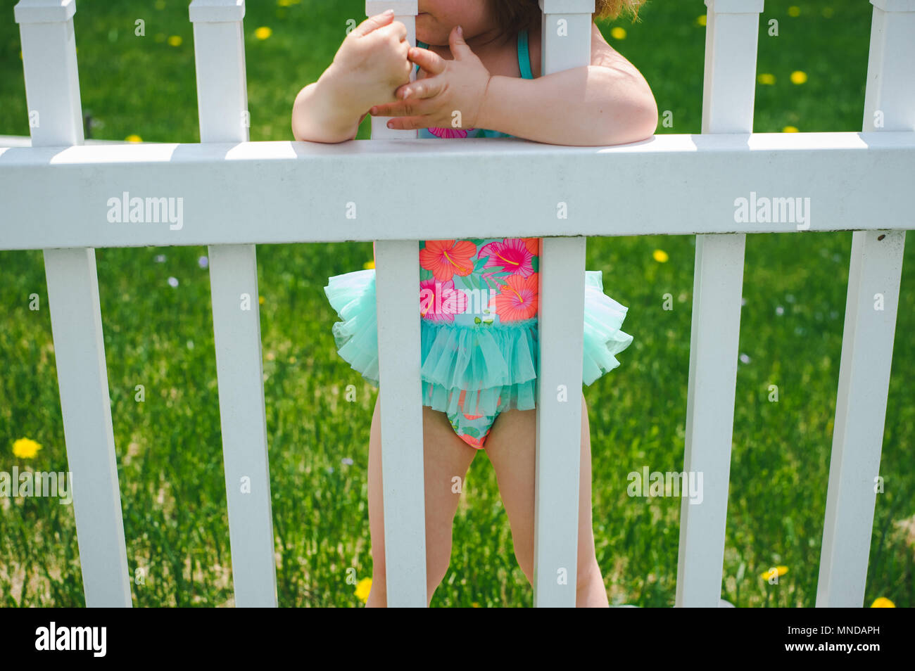 A faceless toddler girl wearing a bright colored bathing suit with flowers on it. - Stock Image
