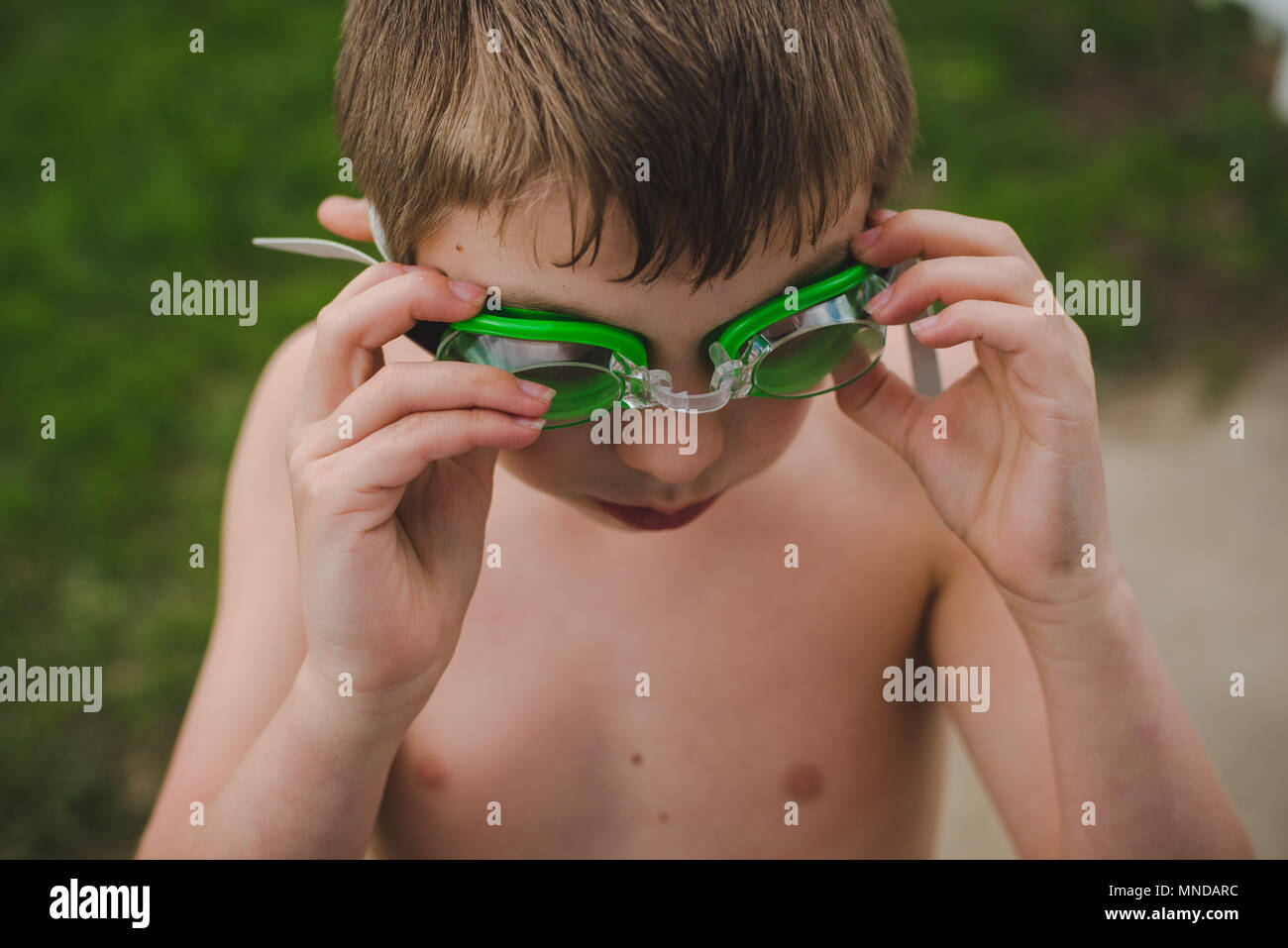 A boy wearing green swimming goggles on a sunny summer day - Stock Image