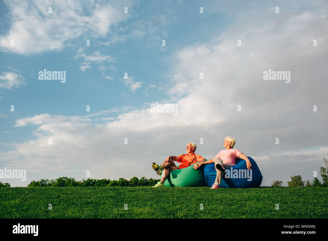 Senior couple sitting on beanbags on grass - Stock Image