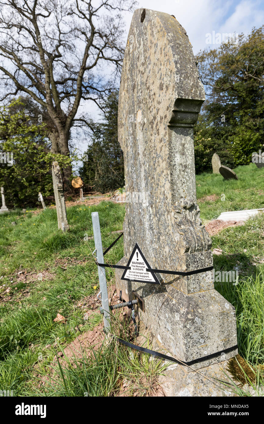 Gravestone held up with post and straps with warning that the memorial is unsafe, Monmouth, UK - Stock Image