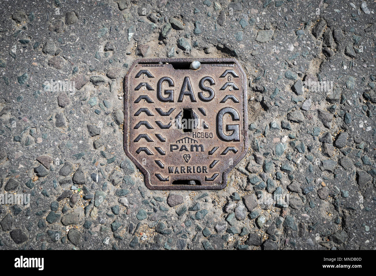 cast iron gas access manhole cover in the street - Stock Image
