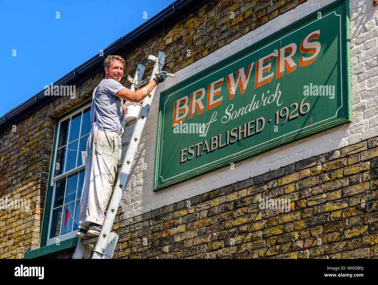 Pianter and decorator painting around a shop sign - Stock Image
