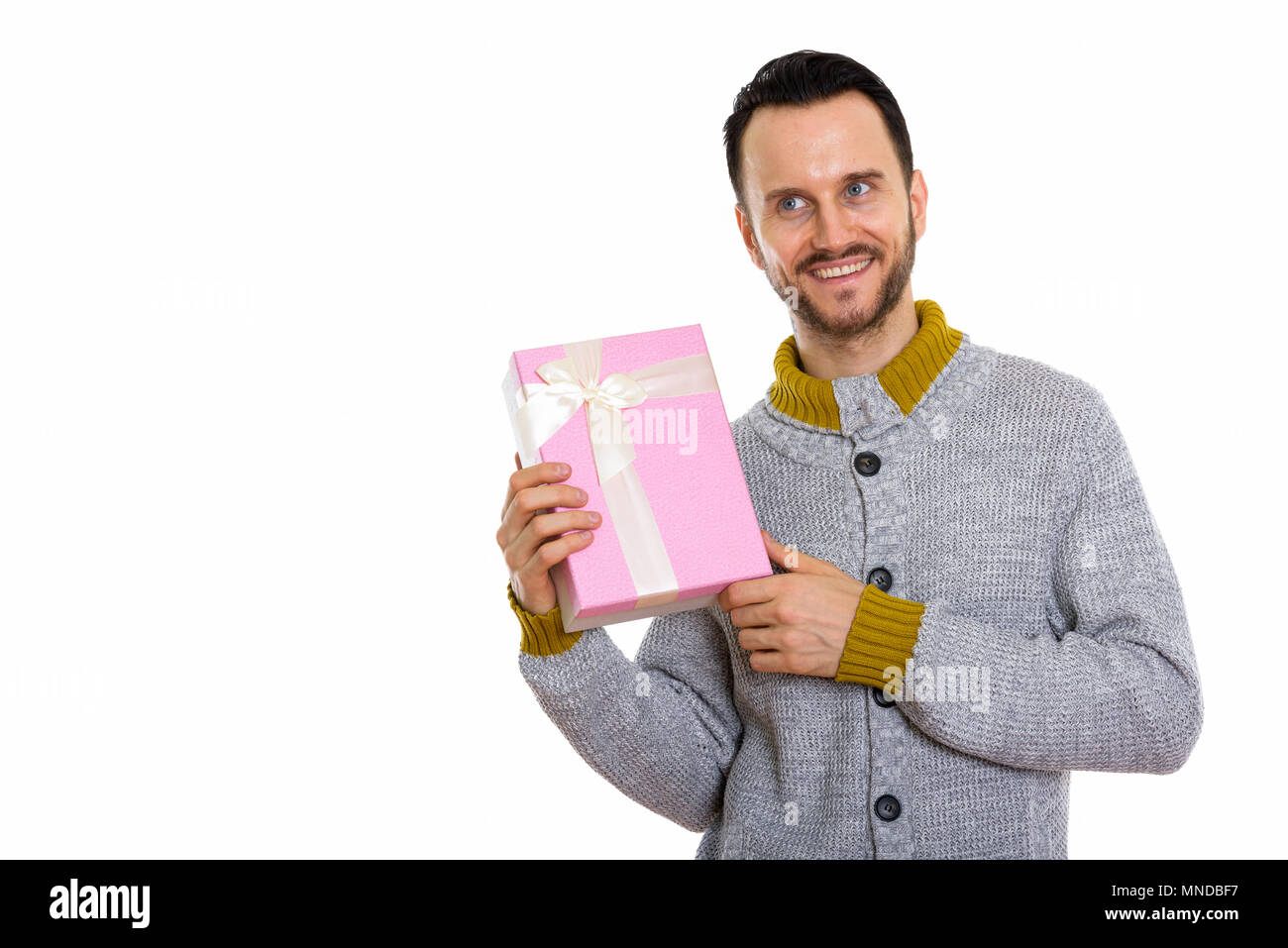 Studio shot of happy young man smiling and guessing gift box ready for Valentine's day - Stock Image