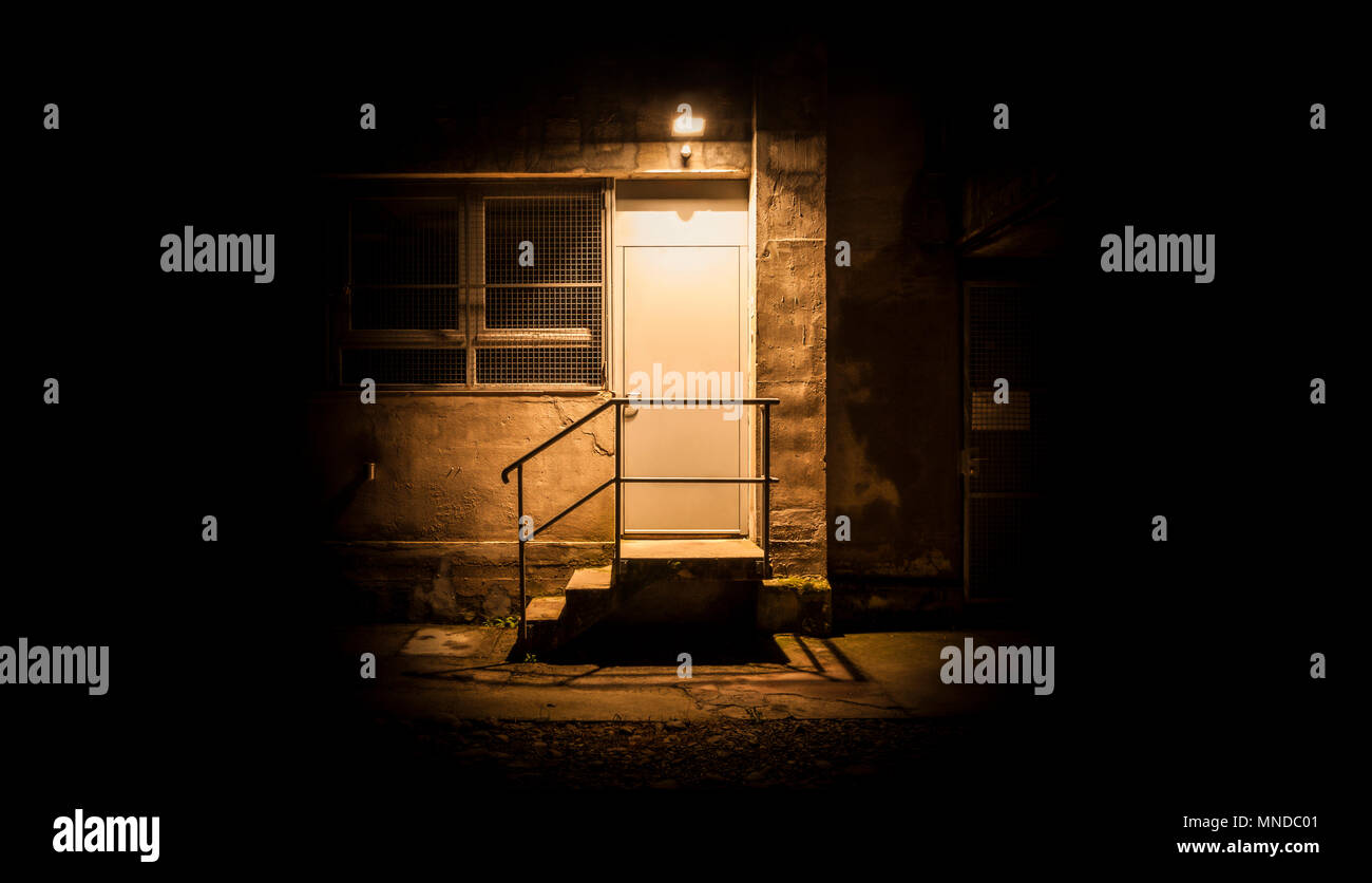 Stairs and door illuminated in the night. The light illuminate only the zone of the door - Stock Image