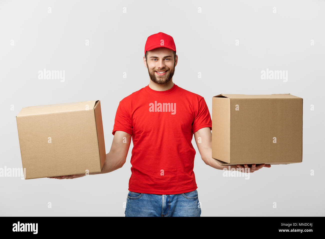 Delivery Concept: Portrait smiling delivery man giving cardbox on white background. - Stock Image