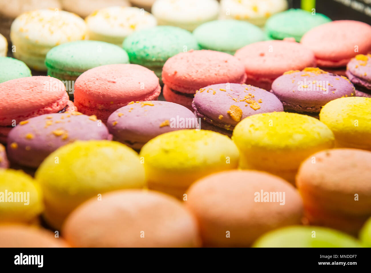 Assortment of Colorful macarons for sale in shop. Rows of macaroons in candy shop, storefront with sweets, cafe showcase. Traditional french almond ca - Stock Image