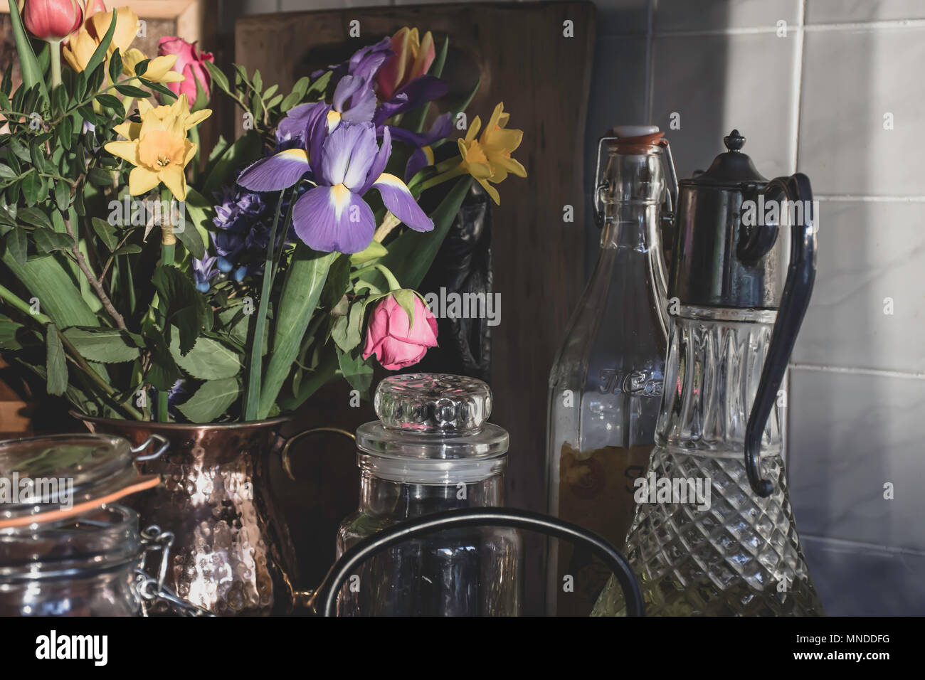 Bouquet of spring flowers in stylish kitchen,Uk.Kitchen decoration, still life composition, natural sunlight from window.Afternoon light.Cut flowers. - Stock Image