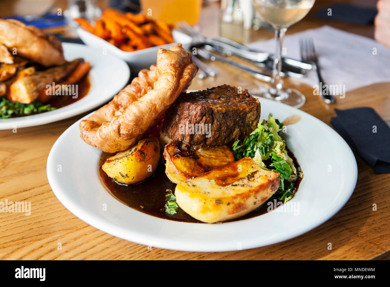 Vegetarian dinner with nut roast, potatoes, yorkshire pudding and gravy - Stock Image