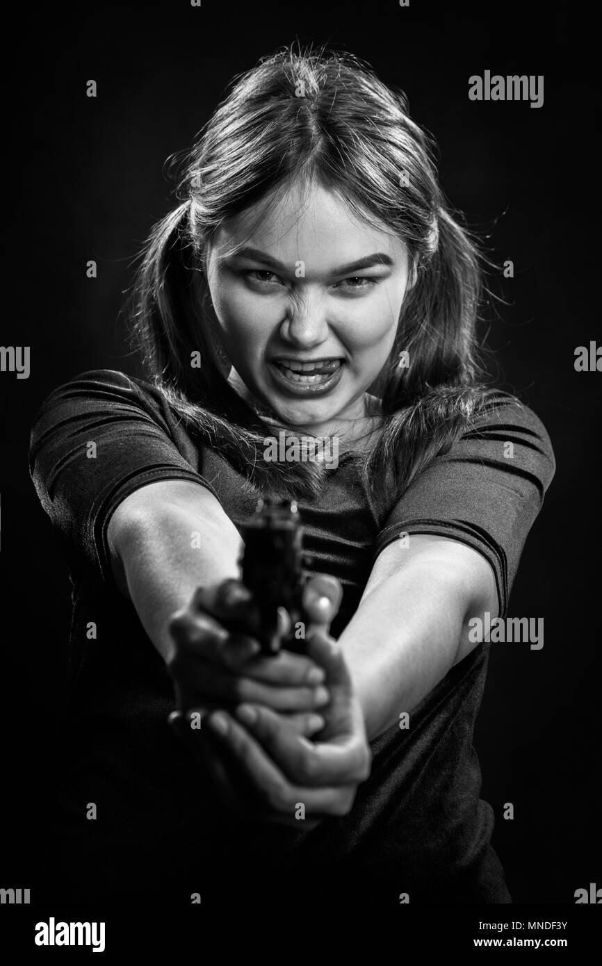 angry girl with gun on black background aiming at camera, monochrome - Stock Image