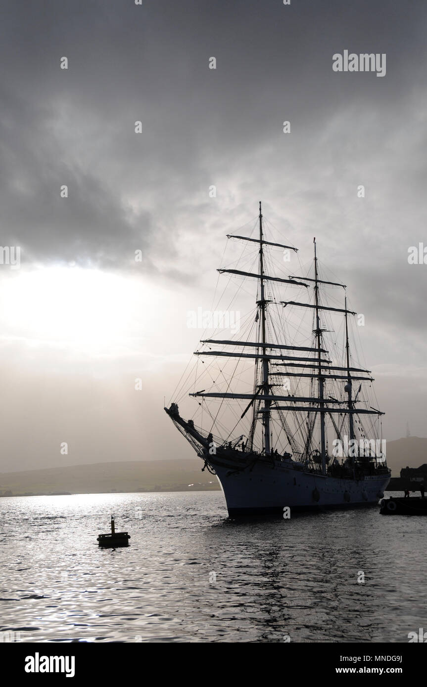 Tallship Sillouette as it is coming into berth in a harbour - Stock Image