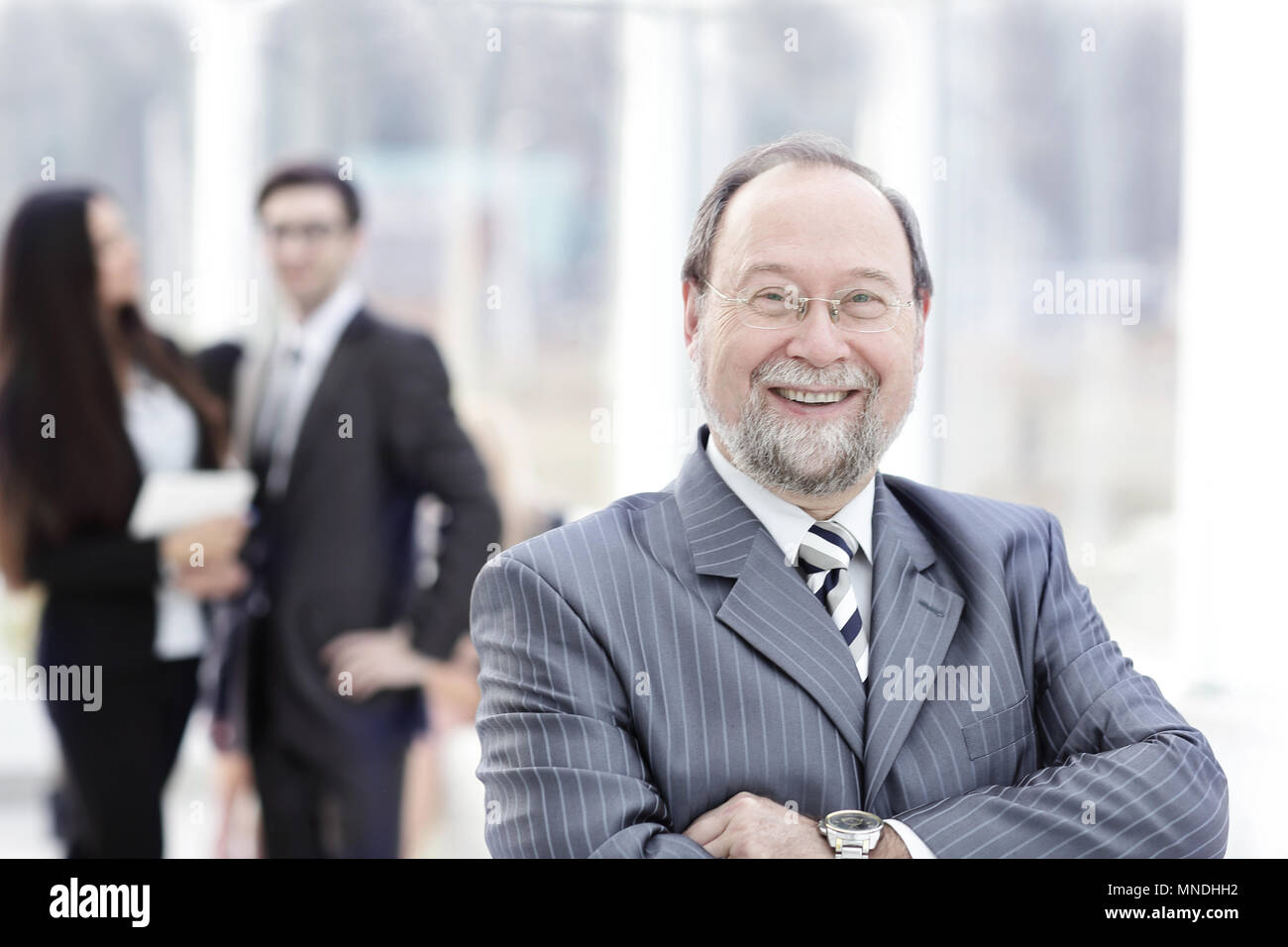 Business man at the office with a group behind him - Stock Image