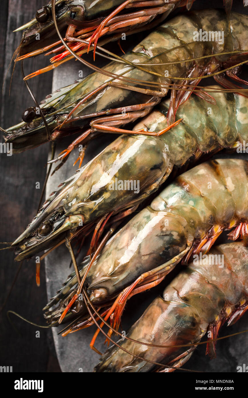 Raw prawns in shells on a stone board, top view. Stock Photo