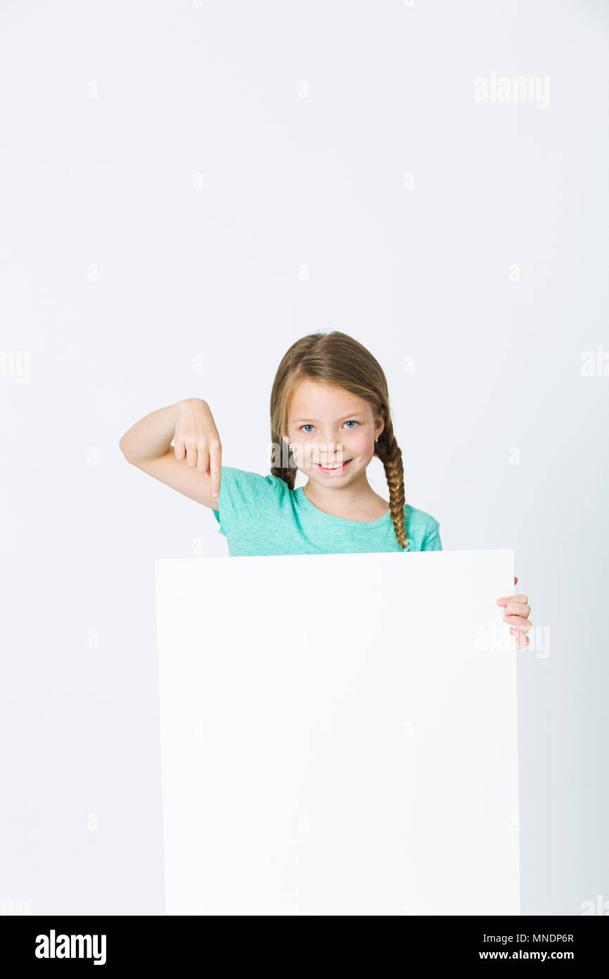 pretty, brunette girl is pointing at white board in front of white background - Stock Image