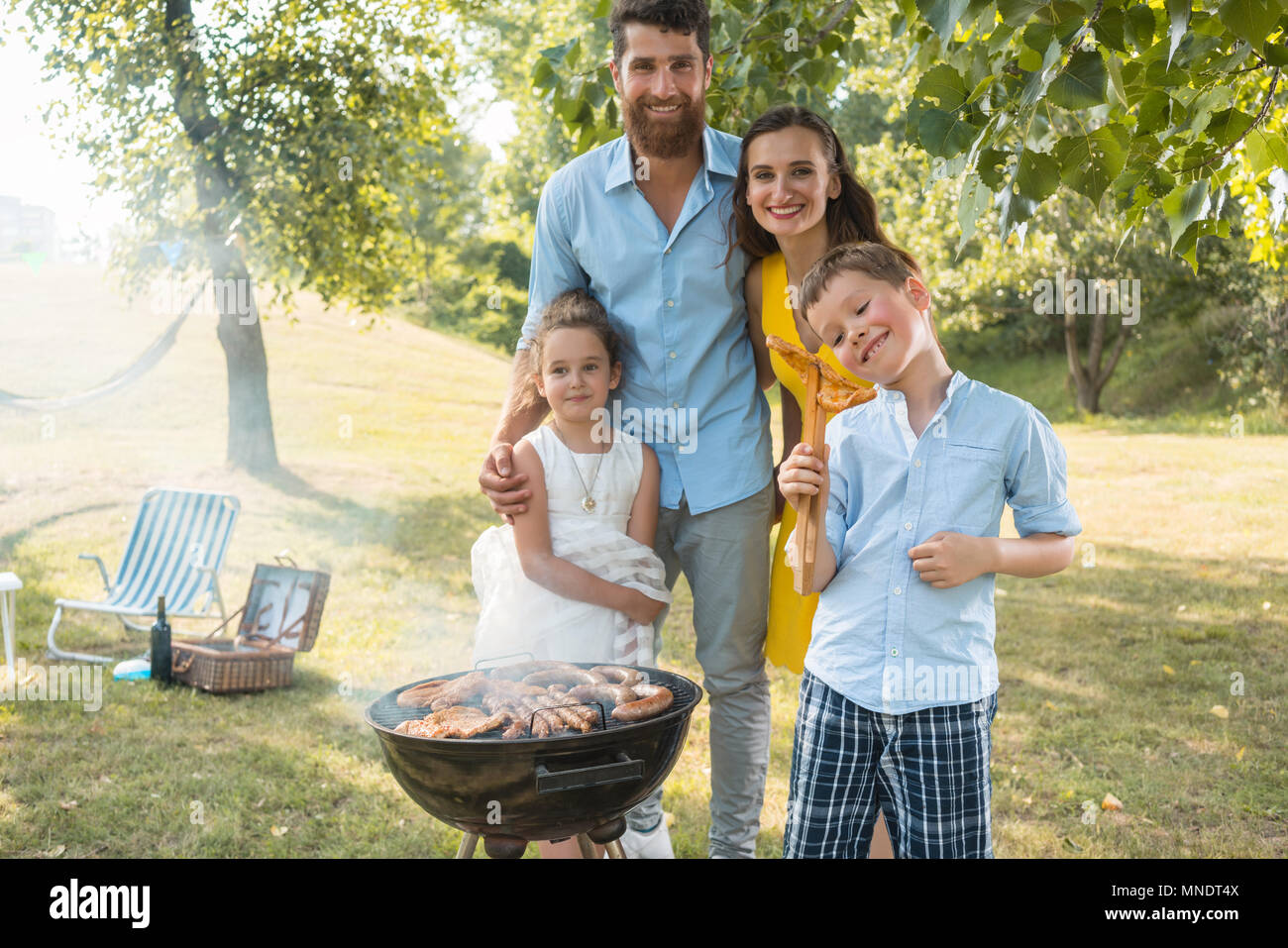 Portrait of happy family with two children standing outdoors near a barbecue - Stock Image