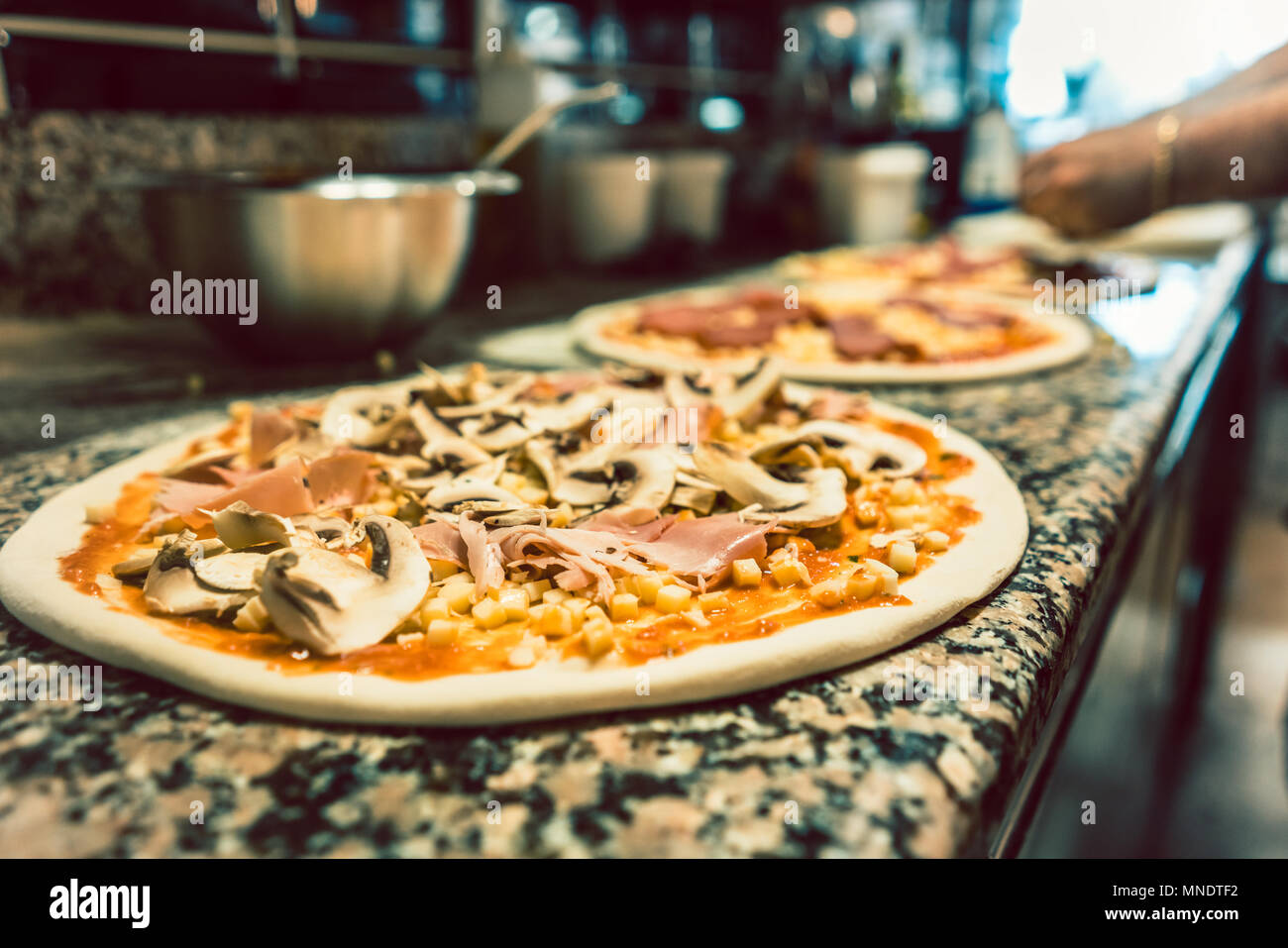 Close-up of unbaked pizza dough topped with mushrooms and prosciutto - Stock Image