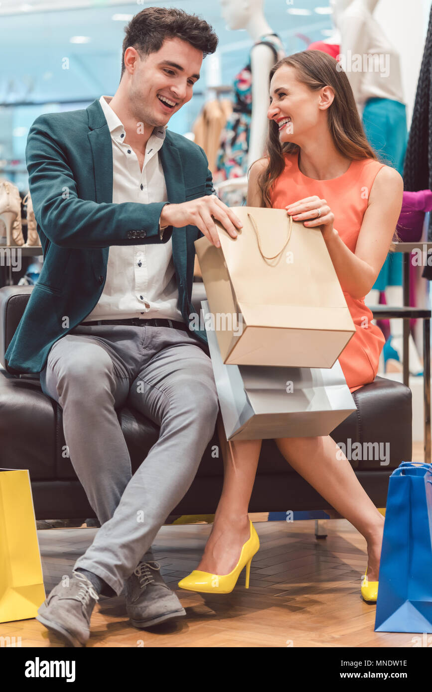 Woman showing her man what she bought in fashion store - Stock Image