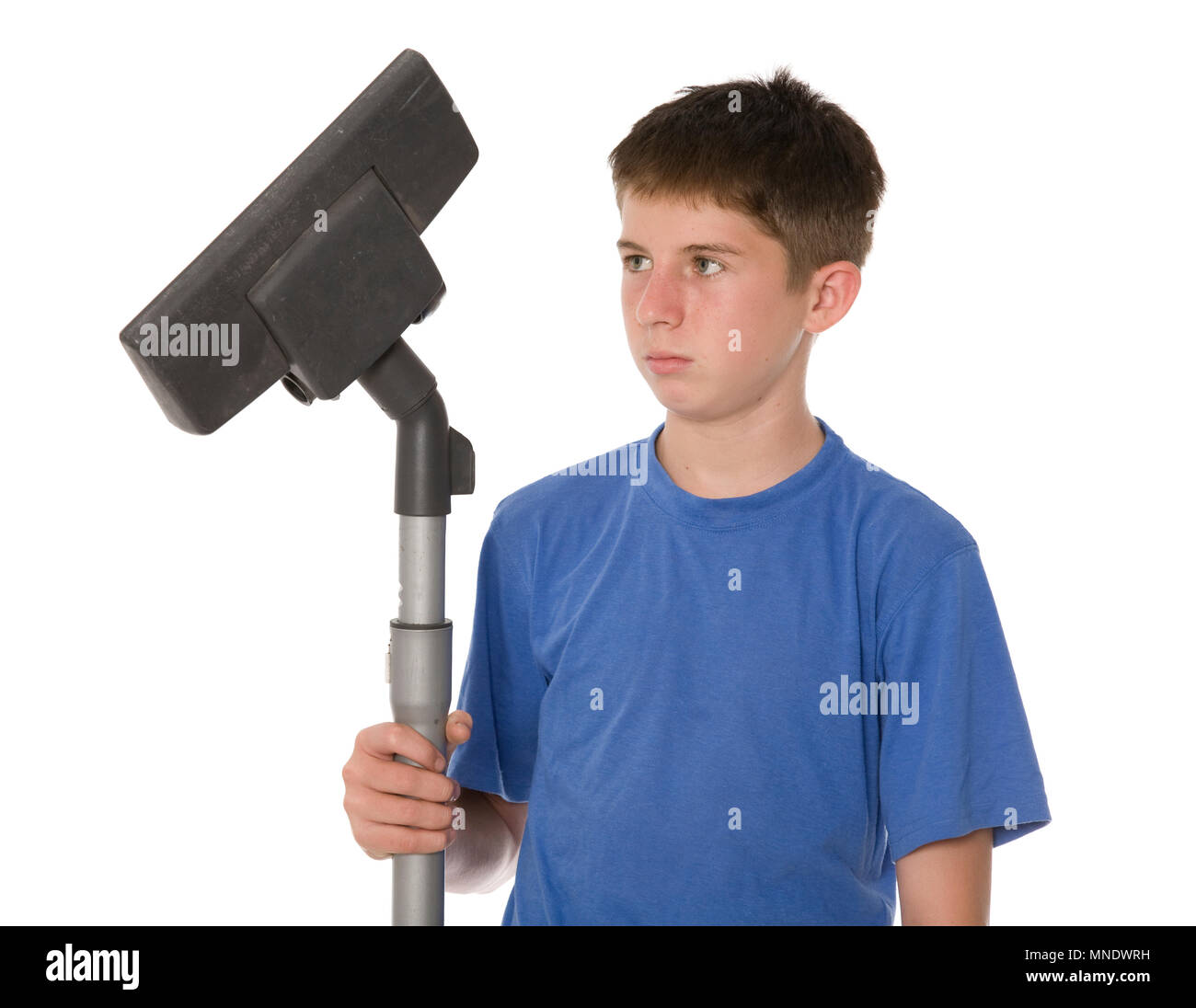 A young teen sulking because he has chores to do. - Stock Image