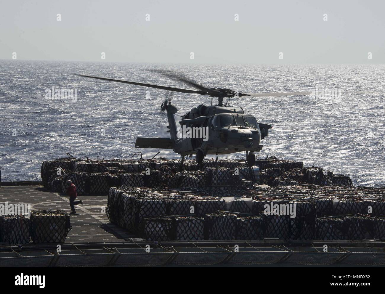 180515-N-AH771-0129 U.S. 5TH FLEET AREA OF OPERATIONS (May 15, 2018) An MH-60s Seahawk, attached to Helicopter Sea Squadron (HSC) 28, tows pallets from the dry cargo and ammunition ship USNS Amelia Earhart (T-AKE 6) to the Wasp-class amphibious assault ship USS Iwo Jima (LHD 7) during a replenishment-at-sea, May 15, 2018, May 15, 2018. Iwo Jima, homeported in Mayport, Fla. is on deployment to the U.S. 5th Fleet area of operations in support of maritime security operations to reassure allies and partners, and preserve the freedom of navigation and the free flow of commerce in the region. (U.S.  Stock Photo