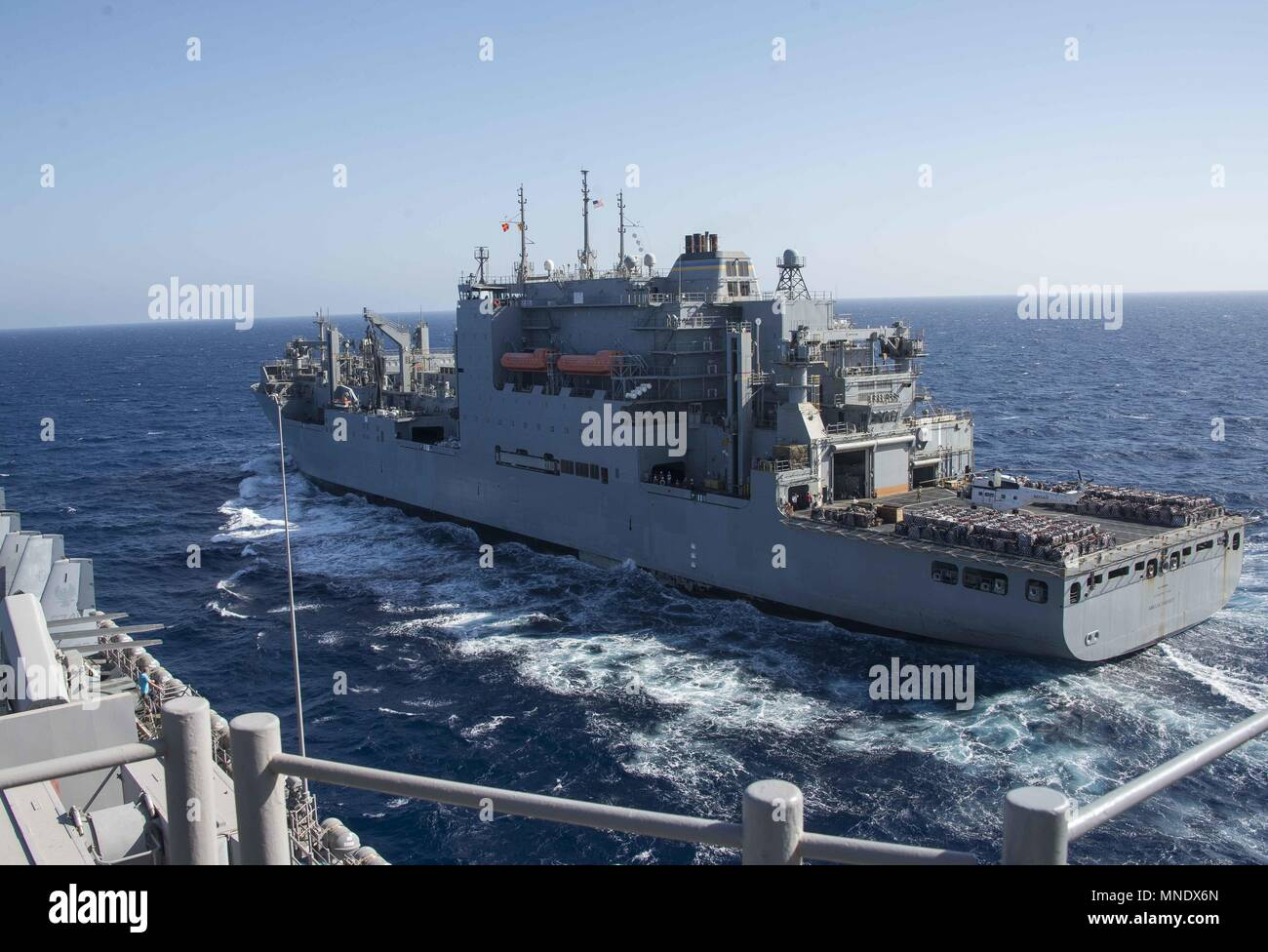 180515-N-AH771-0020 U.S. 5TH FLEET AREA OF OPERATIONS (May 15, 2018) The dry cargo and ammunition ship USNS Amelia Earhart (T-AKE 6) prepares to come alongside the Wasp-class amphibious assault ship USS Iwo Jima (LHD 7) during a replenishment-at-sea, May 15, 2018, May 15, 2018. Iwo Jima, homeported in Mayport, Fla. is on deployment to the U.S. 5th Fleet area of operations in support of maritime security operations to reassure allies and partners, and preserve the freedom of navigation and the free flow of commerce in the region. (U.S. Navy photo by Mass Communication Specialist 3rd Class Danie Stock Photo