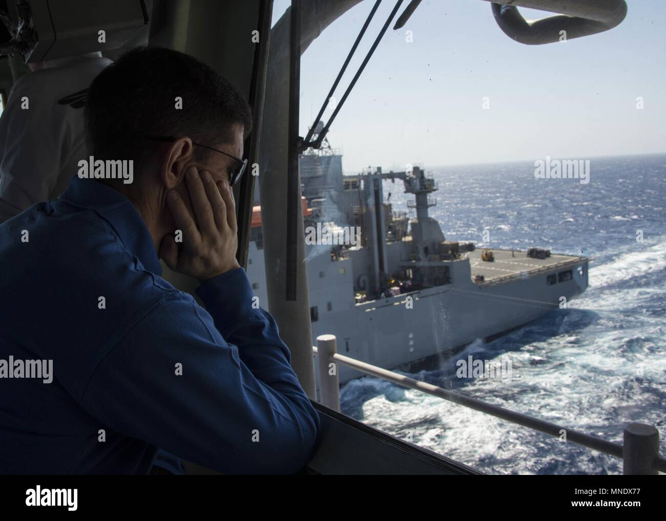 180515-N-AH771-0255 U.S. 5TH FLEET AREA OF OPERATIONS (May 15, 2018) Capt. Darrell S. Canady, executive officer aboard the Wasp-class amphibious assault ship USS Iwo Jima (LHD 7) watches from the starboard side bridge-wing as the ship conducts a replenishment-at-sea with the dry cargo and ammunition ship USNS Amelia Earhart (T-AKE 6), May 15, 2018, May 15, 2018. Iwo Jima, homeported in Mayport, Fla. is on deployment to the U.S. 5th Fleet area of operations in support of maritime security operations to reassure allies and partners, and preserve the freedom of navigation and the free flow of com Stock Photo