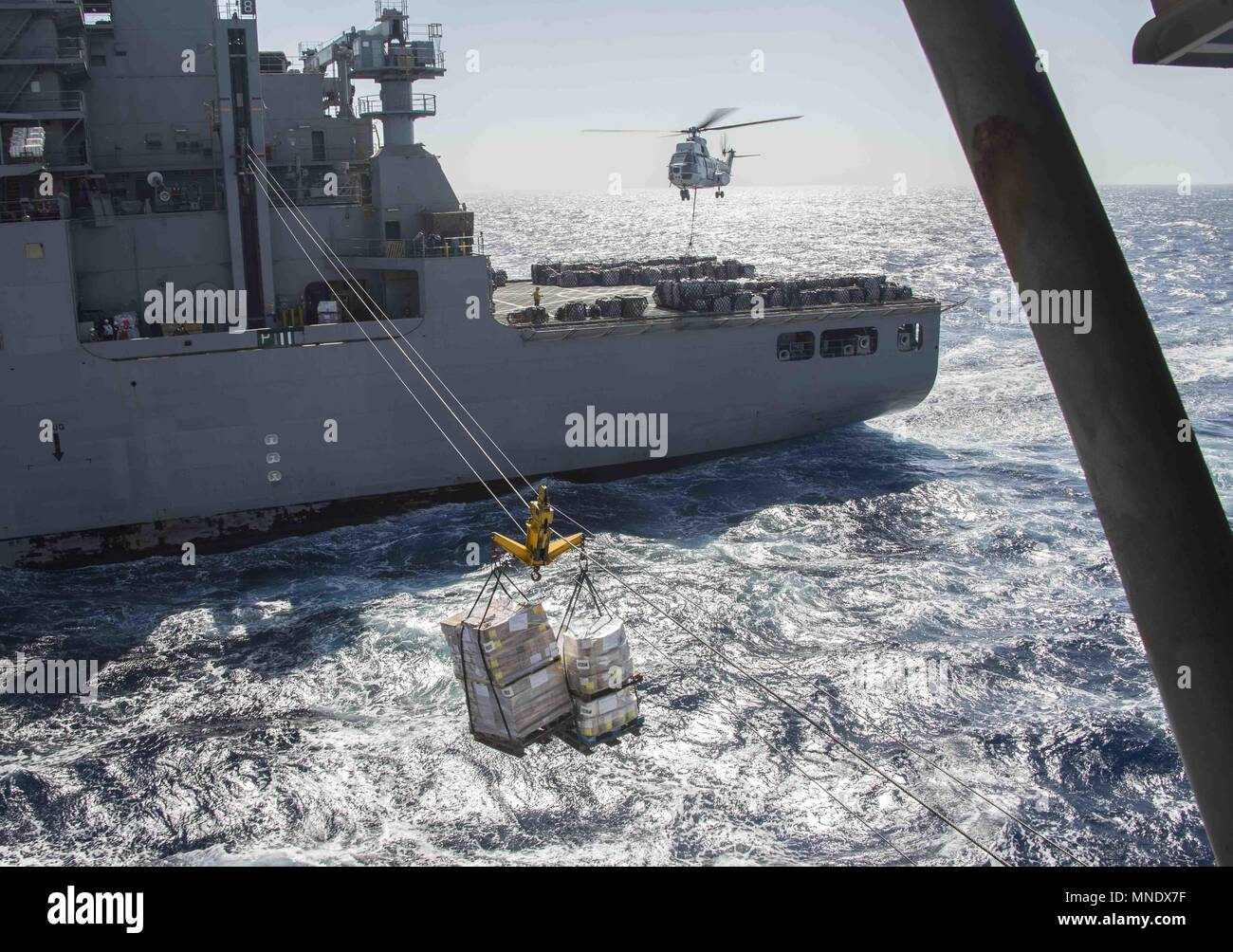 180515-N-AH771-0244 U.S. 5TH FLEET AREA OF OPERATIONS (May 15, 2018) The dry cargo and ammunition ship USNS Amelia Earhart (T-AKE 6) sends pallets of supplies to the Wasp-class amphibious assault ship USS Iwo Jima (LHD 7) during a replenishment-at-sea, May 15, 2018, May 15, 2018. Iwo Jima, homeported in Mayport, Fla. is on deployment to the U.S. 5th Fleet area of operations in support of maritime security operations to reassure allies and partners, and preserve the freedom of navigation and the free flow of commerce in the region. (U.S. Navy photo by Mass Communication Specialist 3rd Class Dan Stock Photo