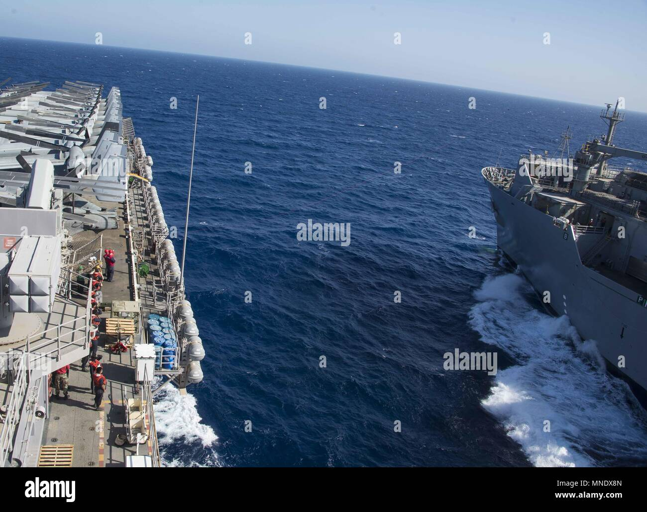 180515-N-AH771-0055 U.S. 5TH FLEET AREA OF OPERATIONS (May 15, 2018) The dry cargo and ammunition ship USNS Amelia Earhart (T-AKE 6) receives the phone and distance line from the Wasp-class amphibious assault ship USS Iwo Jima (LHD 7) during a replenishment-at-sea, May 15, 2018, May 15, 2018. Iwo Jima, homeported in Mayport, Fla. is on deployment to the U.S. 5th Fleet area of operations in support of maritime security operations to reassure allies and partners, and preserve the freedom of navigation and the free flow of commerce in the region. (U.S. Navy photo by Mass Communication Specialist  Stock Photo