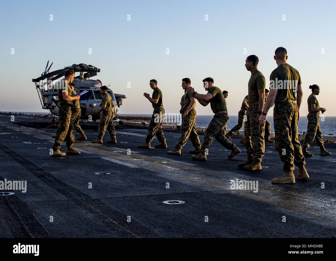 180515-N-ZK016-0002 U.S. 5TH FLEET AREA OF OPERATIONS (May 15, 2018) Marines, assigned to the 26th Marine Expeditionary Unit practice hand-to-hand combat exercises on the flight deck of the Wasp-class amphibious assault ship USS Iwo Jima (LHD 7), May 15, 2018, May 15, 2018. Iwo Jima, homeported in Mayport, Fla. is on deployment to the U.S. 5th Fleet area of operations in support of maritime security operations to reassure allies and partners, and preserve the freedom of navigation and the free flow of commerce in the region. (U.S. Navy photo by Mass Communication Specialist 3rd Class Joe J. Ca Stock Photo