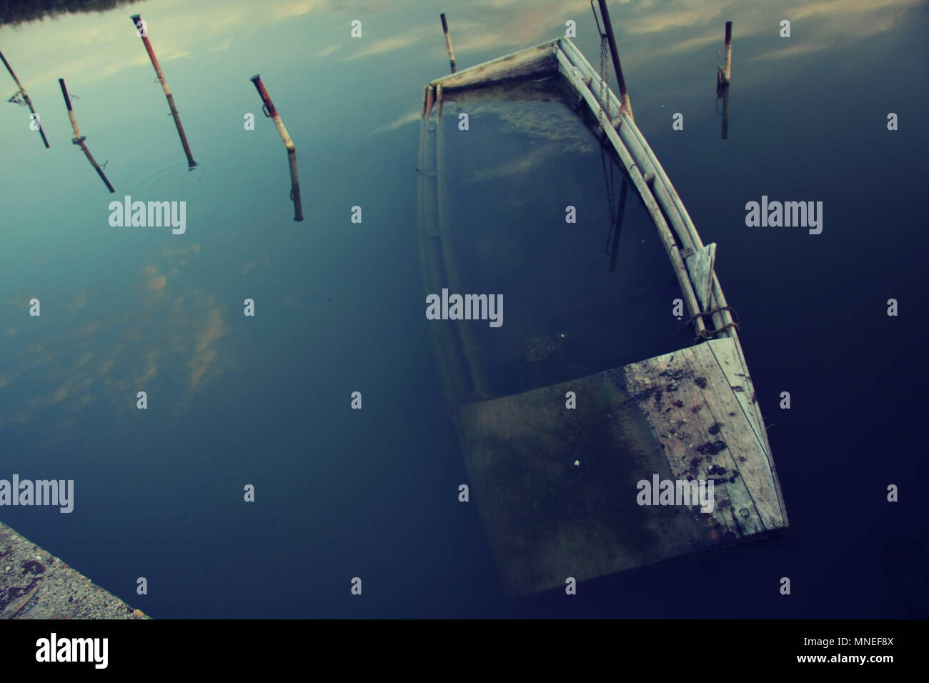Close look of an old wood floating fishing boat what is forgotten and almost sunk into the lake. Rusty iron rods standing around it. - Stock Image