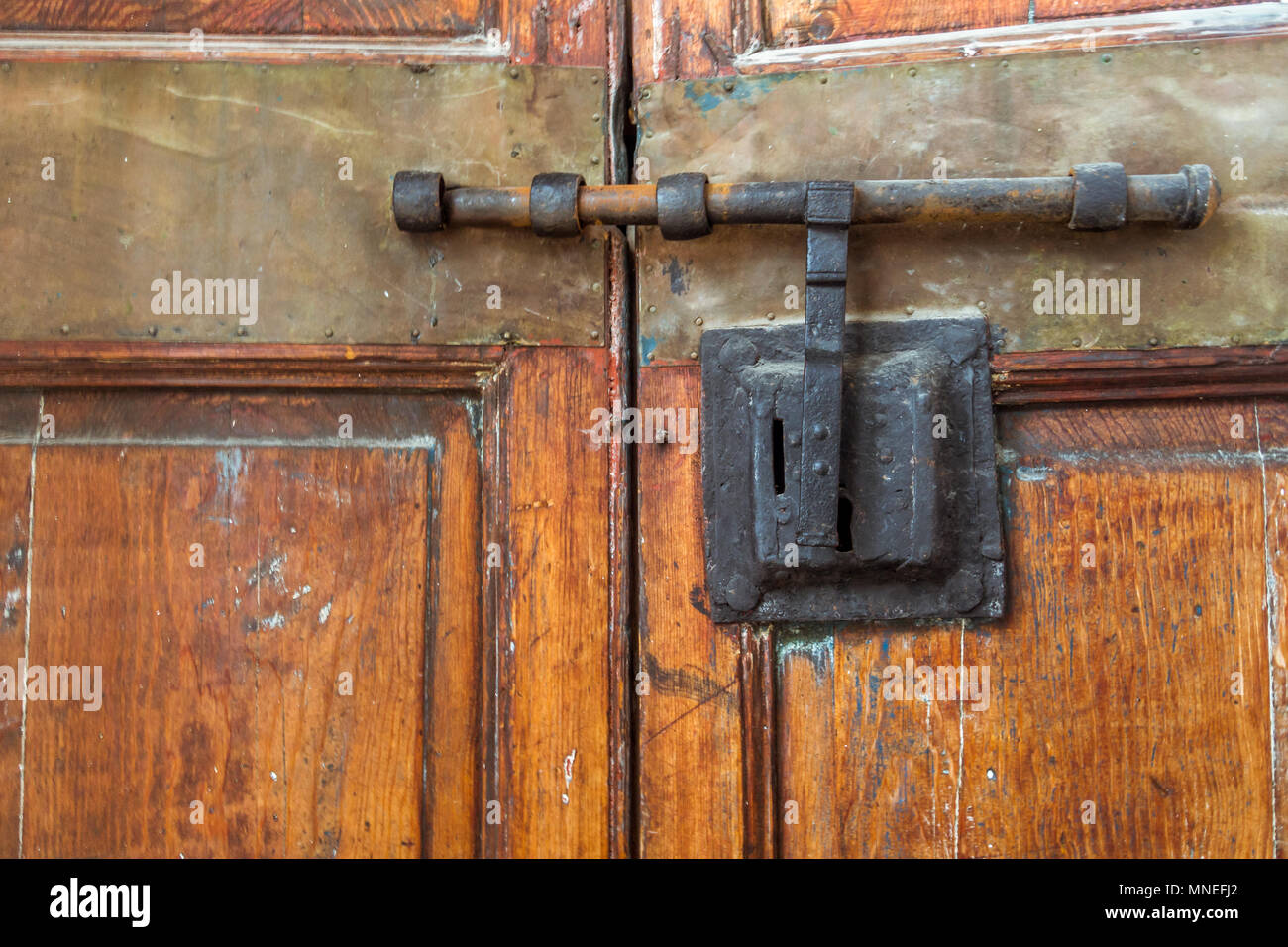 Old Wooden Door Closed With Wrought Iron Bar