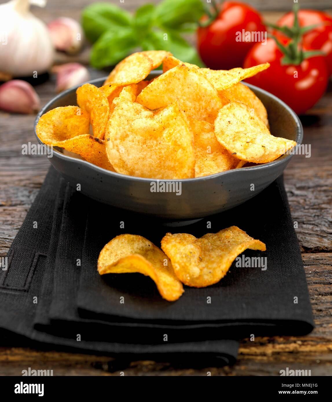 A bowl of tomato crisps - Stock Image