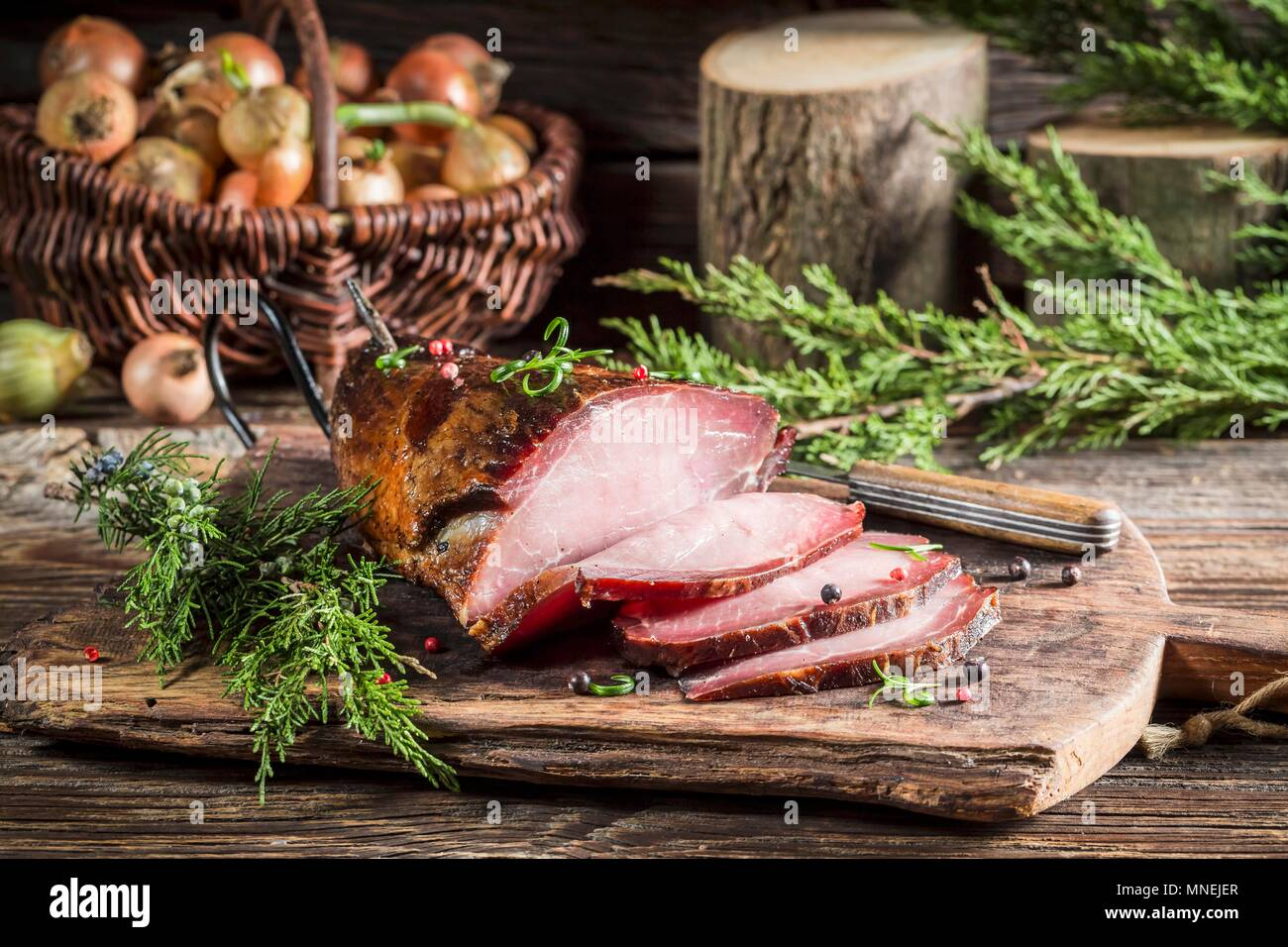 Smoked ham with juniper berries on a wooden chopping board Stock Photo