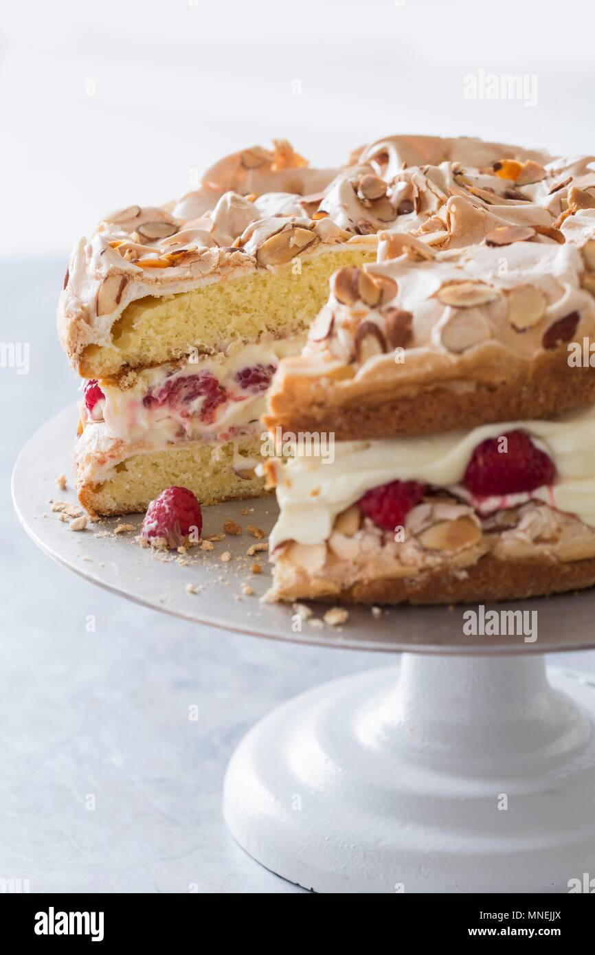 Quick cake made from sponge cake, cream and raspberries with a meringue topping on a cake stand - Stock Image