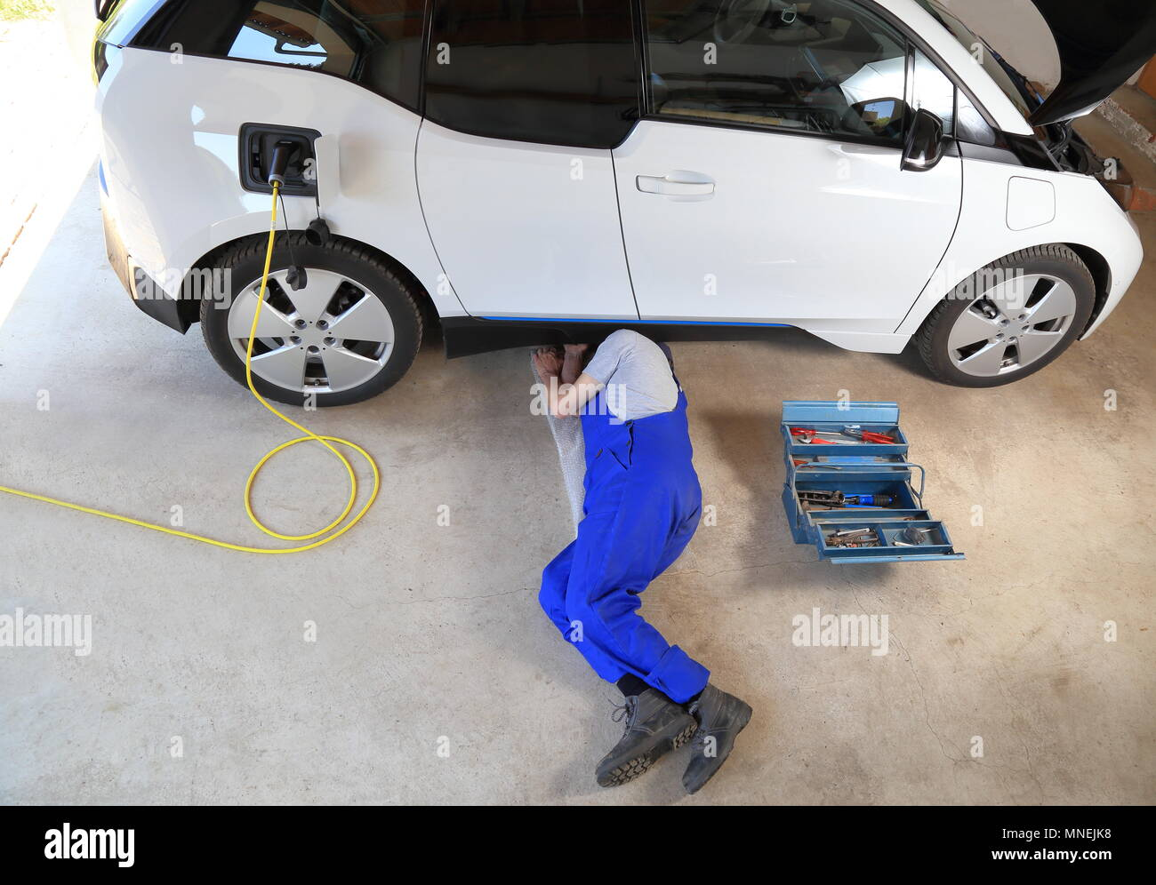 A Mechanic repairing an electric driven car at garage Stock Photo